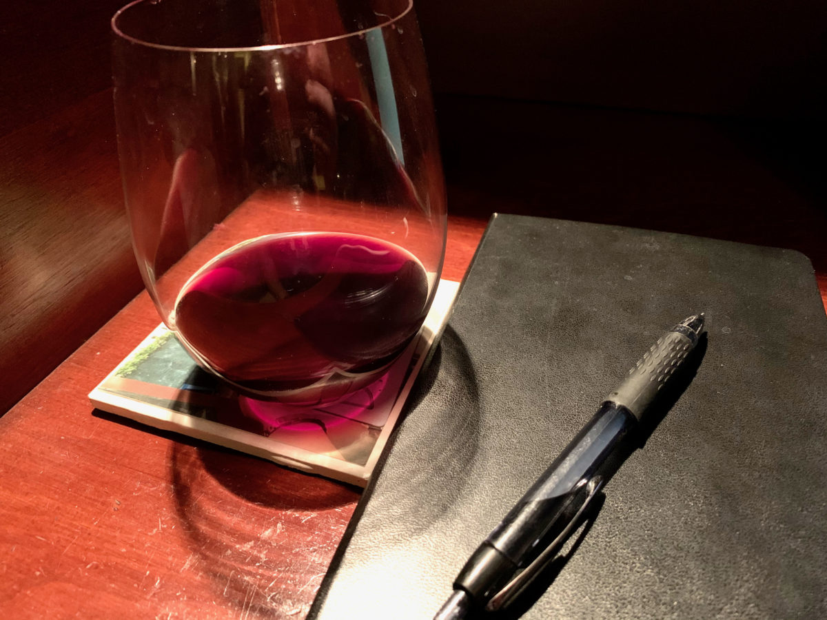 glass of red wine and moleskine notebook