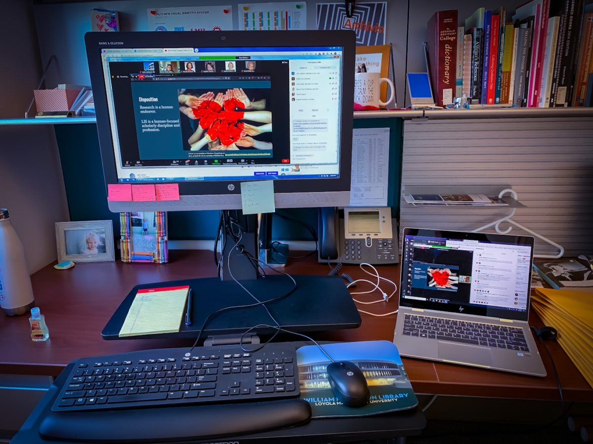 View of author's desk including screen, laptop and books.
