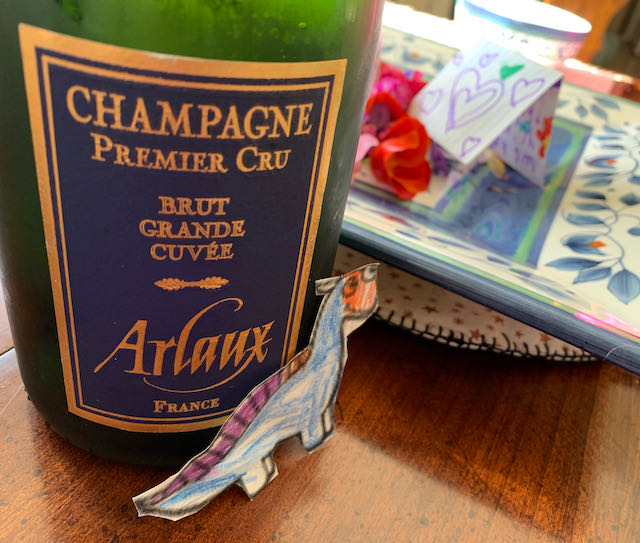 arlaux champagne bottle and small paper dinosaur